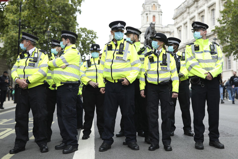 Police officers wearing face masks stand guard during a protest opposed to COVID-19 pandemic restrictions, in Trafalgar Square, London, Saturday, Aug. 29, 2020. This protest shows solidarity with a protest held in Germany where tens of thousands of people gathered at the German capital's iconic Brandenburg Gate in the morning before streaming down the Unter den Linden boulevard in a show of defiance against Germany's coronavirus prevention measures. (Yui Mok/PA via AP)