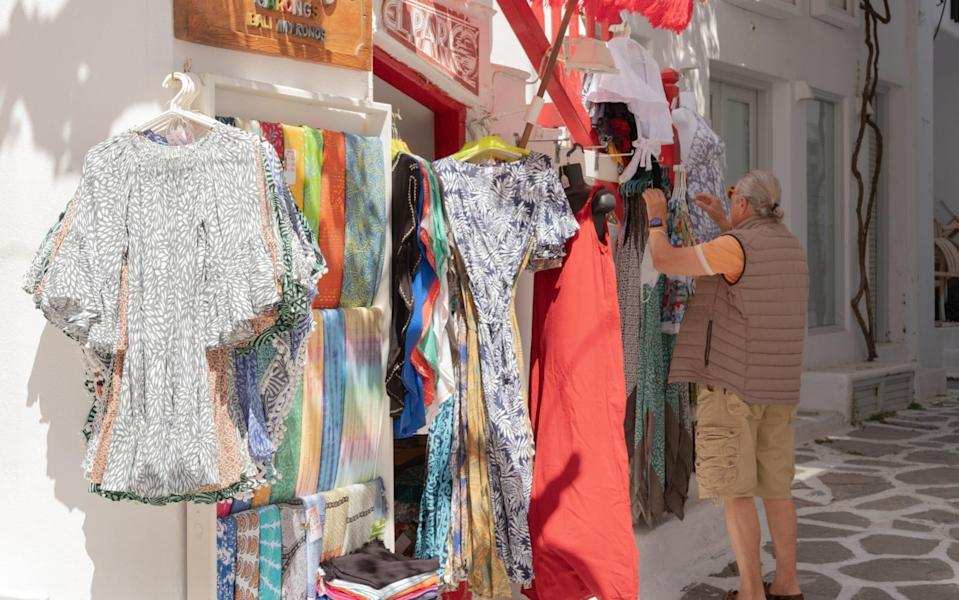 A shop owner arranges clothing for sale outside his store - Getty