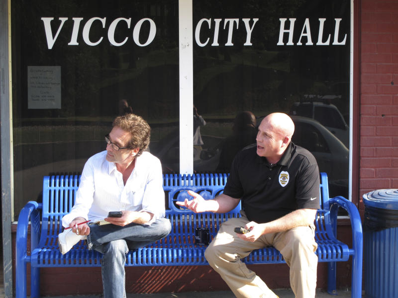 In this Monday, Sept. 16, 2013 photo, Vicco Mayor Johnny Cummings, left, and Police Chief Tony Vaughn sit in front of the city hall in the Appalachian town of Vicco, KY, Eight months after the tiny town took a stand against gay-based discrimination, it's basking in a flurry of attention and even an infusion of much-needed cash. All that hoopla has its openly gay mayor dreaming of reviving a place that had long seemed past its prime. (AP Photo/Bruce Schreiner)