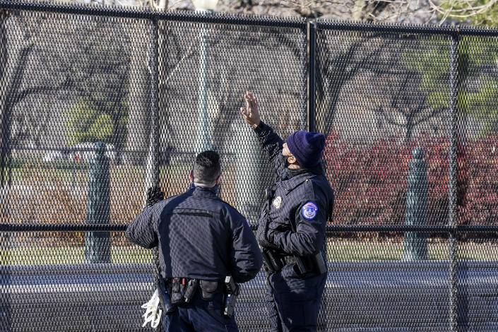 Capitol police officers look at fencing that was installed around the exterior of the Capitol grounds, Thursday, Jan. 7, 2021 in Washington. The House and Senate certified the Democrat's electoral college win early Thursday after a violent throng of pro-Trump rioters spent hours Wednesday running rampant through the Capitol. A woman was fatally shot, windows were bashed and the mob forced shaken lawmakers and aides to flee the building, shielded by Capitol Police. (AP Photo/John Minchillo)