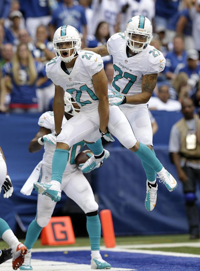 Miami Diolphins' Brent Grimes (21) celebrates with Jimmy Wilson (27) after Grimes intercepted a pass in the end zone intended for Indianapolis Colts' Reggie Wayne during the second half an NFL football game Sunday, Sept. 15, 2013, in Indianapolis. (AP Photo/Michael Conroy)