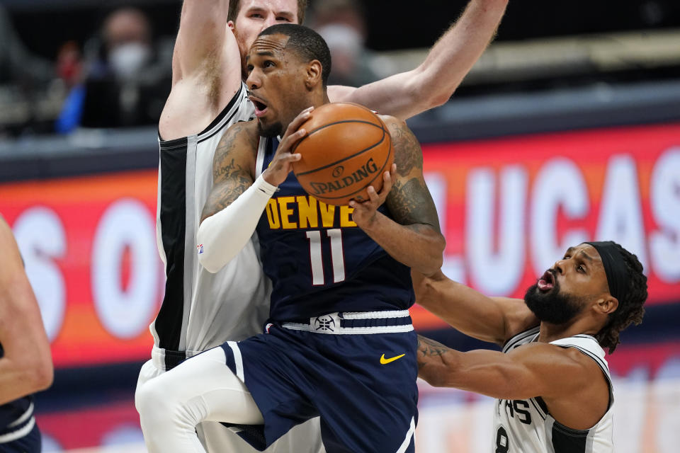 Denver Nuggets guard Monte Morris, front left, drives to the basket past San Antonio Spurs center Jakob Poeltl, back left, and guard Patty Mills in the second half of an NBA basketball game Friday, April 9, 2021, in Denver. (AP Photo/David Zalubowski)