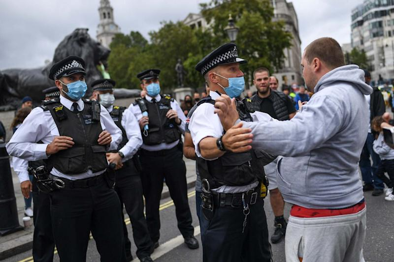An officer pushes back an unmasked protester at the Unite for Freedom rally (Getty Images)