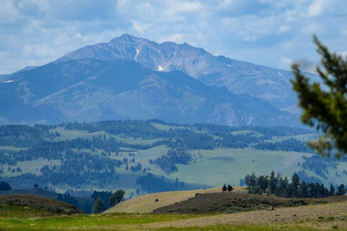 A couple of park guests take in a panoramic view of Electric Peak and the Gallatin Range from Blacktail Plateau in Yellowstone National Park, July 24, 2020.