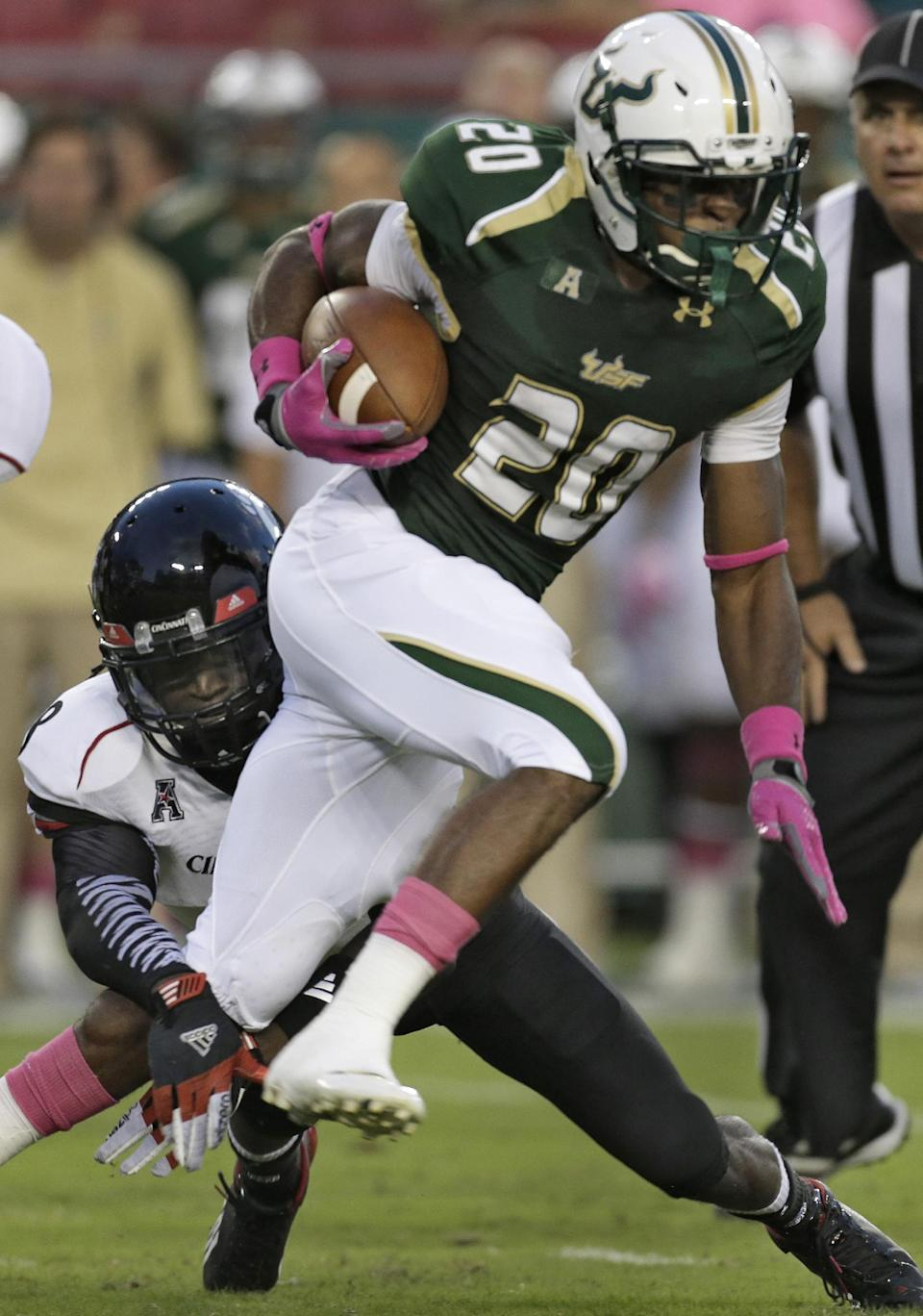 South Florida's Marcus Shaw (20) is tripped up by Cincinnati's Adrian Witty, left, during the first quarter of an NCAA college football game on Saturday, Oct. 5, 2013, in Tampa, Fla. (AP Photo/Chris O'Meara)