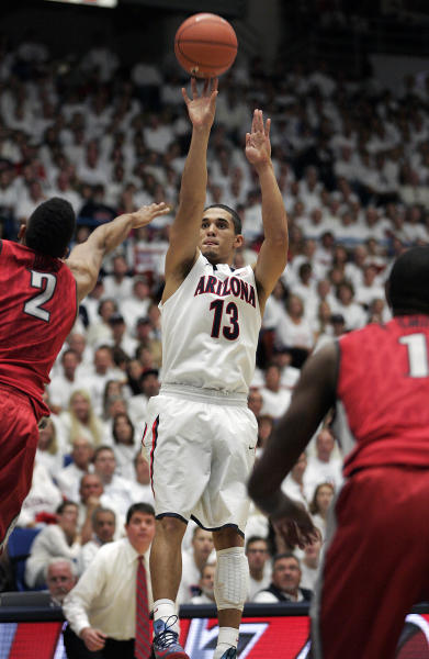 Arizona's Nick Johnson (13) shoots for two points between UNLV's Khem Birch (2) and Roscoe Smith (1) in the first half of an NCAA college basketball game on Saturday, Dec. 7, 2013, in Tucson, Ariz. Arizona won 63-58. (AP Photo/John MIller)