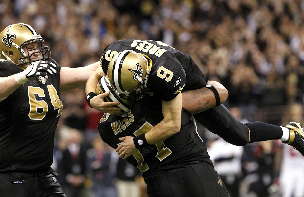 New Orleans Saints quarterback Drew Brees (9) celebrates with offensive guard Carl Nicks (77) and tackle Zach Strief (64) after throwing a touchdown pass and breaking the league record for single-season passing yardage, held by Dan Marino, in the fourth quarter of an NFL football game against the Atlanta Falcons in New Orleans, Monday, Dec. 26, 2011. (AP Photo/Rusty Costanza)