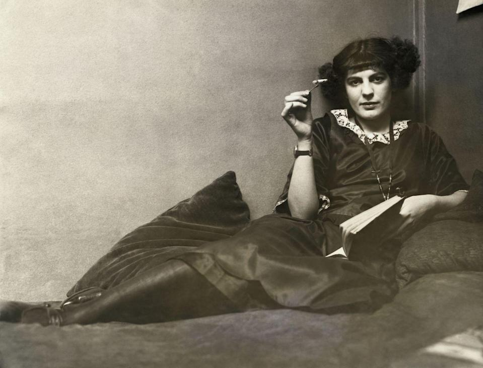 "<p>A flapper woman relaxes on a chaise lounge with a cigarette in one hand and a book in the other. </p><p>""Flappers"" were <a href=""https://www.history.com/news/flappers-roaring-20s-women-empowerment"" rel=""nofollow noopener"" target=""_blank"" data-ylk=""slk:typically young women"" class=""link rapid-noclick-resp"">typically young women</a> in the 1920s who enjoyed jazz and cigarettes while sporting a ""bob"" hairstyle and a knee-length skirt.</p>"