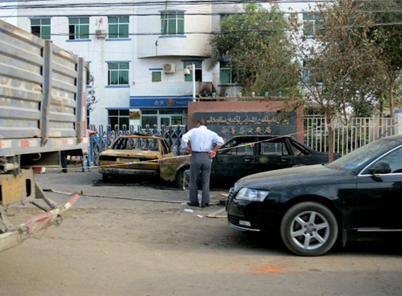 This June 27, 2013 photo shows destroyed vehicles in front of a police station in Lukqun township, Xinjiang, China, a day after a violent rampage occurred. Violent incidents have spread over the past week in a tense minority region of western China, just days before the fourth anniversary of a bloody clash between minority Uighurs and the ethnic Han majority that left almost 200 people dead and resulted in a major security clampdown. (AP Photo/Kyodo News) JAPAN OUT, MANDATORY CREDIT