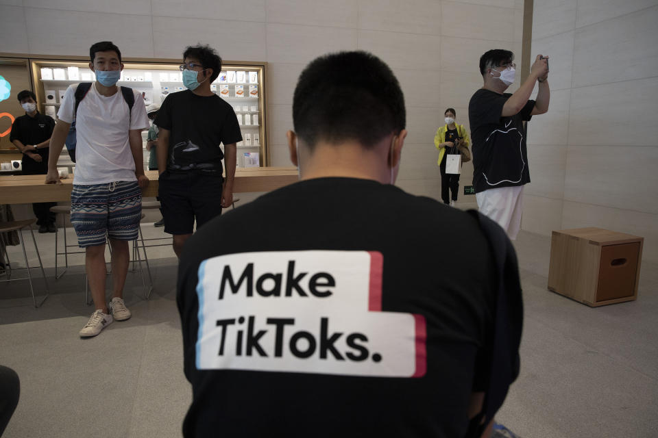 A man wearing a shirt promoting TikTok is seen at an Apple store in Beijing