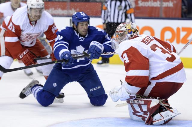 Detroit Red Wings goalie Petr Mrazek, right, makes a save as Toronto Maple Leafs' Troy Bodie, center, looks for a rebound and Red Wings' Xavier Ouellet defends during second-period preseason NHL hockey game action in Toronto, Saturday Sept. 28, 2013. (AP Photo/The Canadian Press, Frank Gunn)