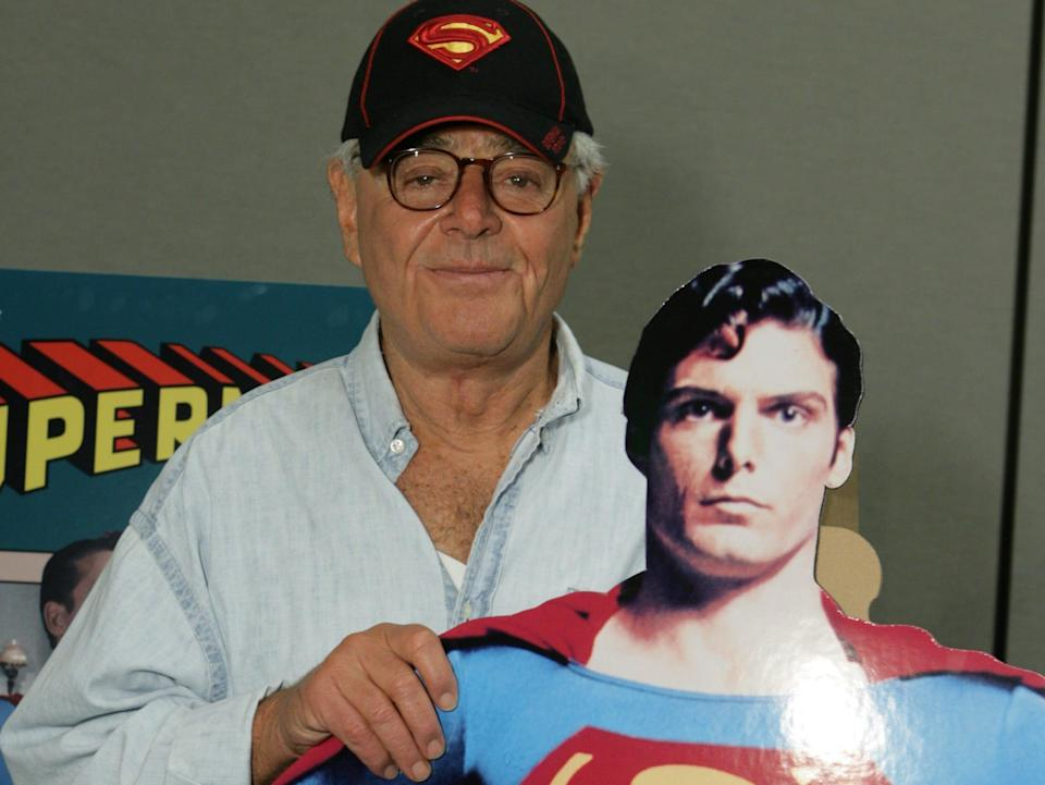 Richard Donner wearing a hat with the Superman symbol and holding a Superman cutout