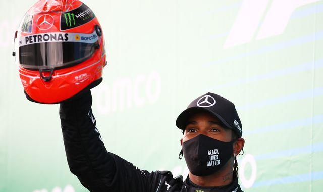 Lewis Hamilton lifts Schumacher's old helmet after equalling German's F1 wins record