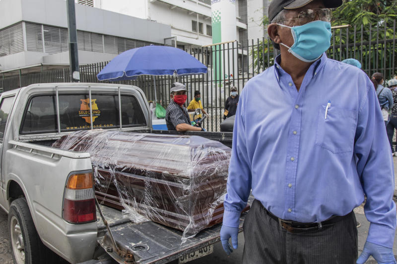 A coffin with the body of a recently deceased person sits in the bed of a pickup truck before burial, outside Teodoro Maldonado Hospital in Guayaquil, Ecuador, Monday, April 6, 2020. Guayaquil, a normally bustling city that has become a hot spot in Latin America as the coronavirus pandemic spreads, also has untold numbers dying of unrelated diseases that can't be treated because hospitals are overwhelmed. (AP Photo/Luis Perez)