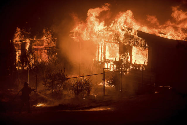 <p>A firefighter sprays water as flames from a wildfire consume a residence near Oroville, Calif., on Sunday, July 9, 2017. Evening winds drove the fire through several neighborhoods leveling homes in its path. (AP Photo/Noah Berger) </p>