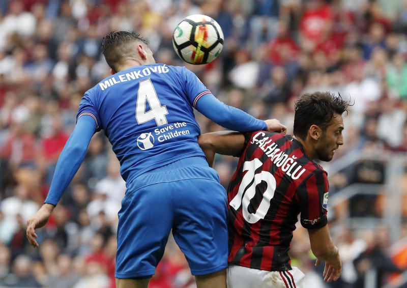 Fiorentina's Nikola Milenkovic, left, jumps for the ball with AC Milan's Hakan Calhanoglu during the Serie A soccer match between AC Milan and Fiorentina at the San Siro stadium in Milan, Italy, Sunday, May 20, 2018. (AP Photo/Antonio Calanni)