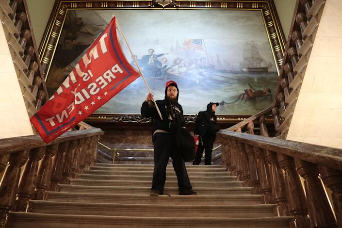 <p>A protester holds a Trump flag inside the US Capitol Building near the Senate Chamber</p> (Getty images)