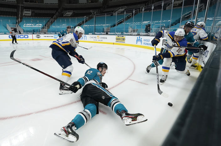 San Jose Sharks left wing Rudolfs Balcers (92) falls in front of St. Louis Blues center Brayden Schenn, right front, during the second period of an NHL hockey game in San Jose, Calif., Saturday, Feb, 27, 2021. (AP Photo/Tony Avelar)