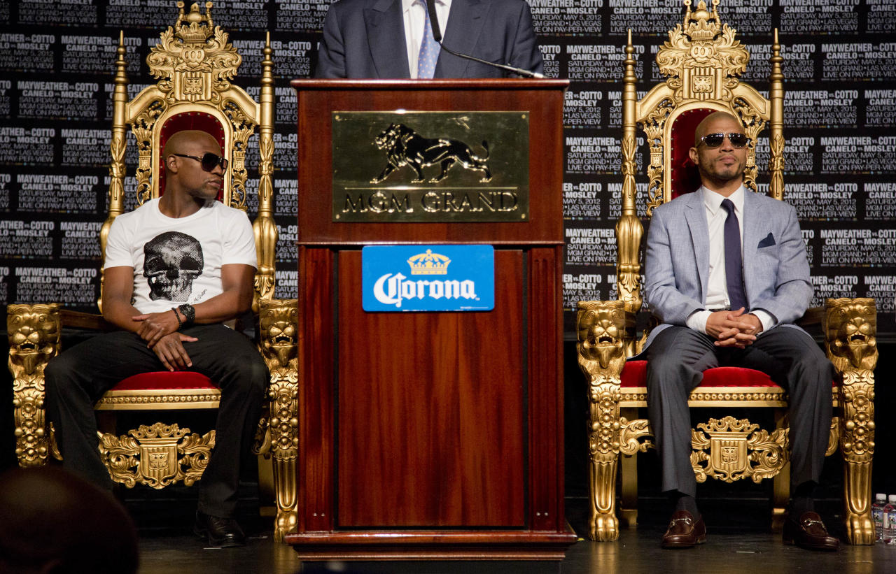 Floyd Mayweather Jr., left, and Miguel Cotto wait to speak during a news conference, Wednesday, May 2, 2012, in Las Vegas. Mayweather and Cotto will fight for the WBC super welterweight diamond belt on Saturday. (AP Photo/Julie Jacobson)