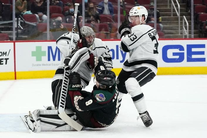 Arizona Coyotes right wing Clayton Keller (9) gets shoved into Los Angeles Kings goaltender Jonathan Quick, left, by Kings defenseman Tobias Bjornfot (33) during the first period of an NHL hockey game Monday, May 3, 2021, in Glendale, Ariz. (AP Photo/Ross D. Franklin)