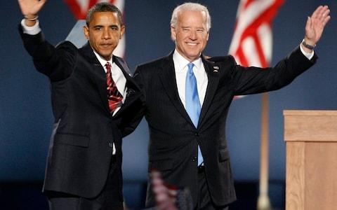 Barack Obama and Joe Biden wave to a crowd of supporters - Credit: REUTERS/Jim Bourg