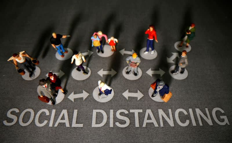 """Small toy figures are placed on a printed background with words """"Social distancing"""" in this illustration"""