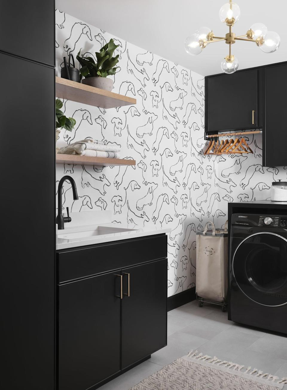 <p>Lucas and Laney's new laundry room has tons of storage space from floating shelves to pantry cabinetry. Chip and Joanna also gave the room a relaxed feel by using puppy patterned wallpaper in honor of the couple's dachshunds. </p>