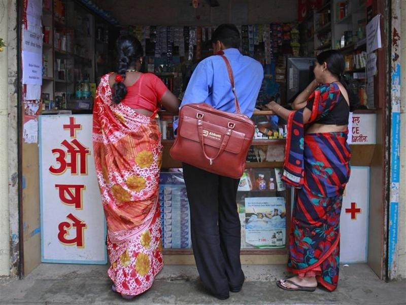 A medical representative with Abbott talks to a chemist at a market in Pune
