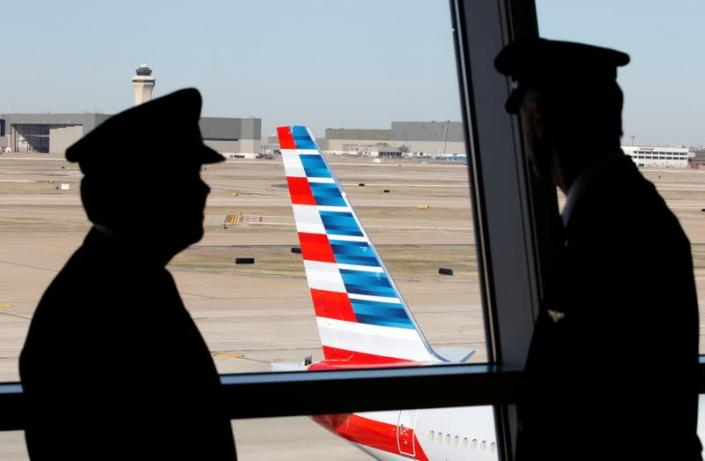 FILE PHOTO: Pilots talk as they look at the tail of an American Airlines aircraft f at Dallas-Ft Worth International Airport