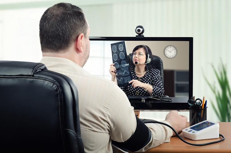 Man sitting at laptop talking to doctor with X-ray in her hands