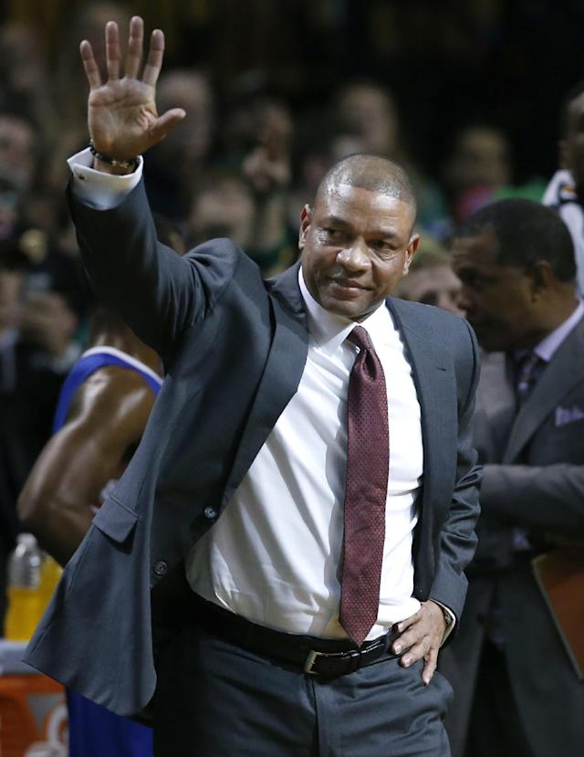 Current Los Angeles Clippers head coach and former Boston Celtics head coach Doc Rivers waves during a video tribute to him for his first time back to the TD Garden, after the first quarter of an NBA basketball game in Boston, Wednesday, Dec. 11, 2013. (AP Photo/Elise Amendola)