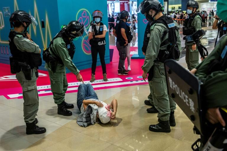 A  police officer points at a woman lying on the ground after being searched during a demonstration in a mall in Hong Kong