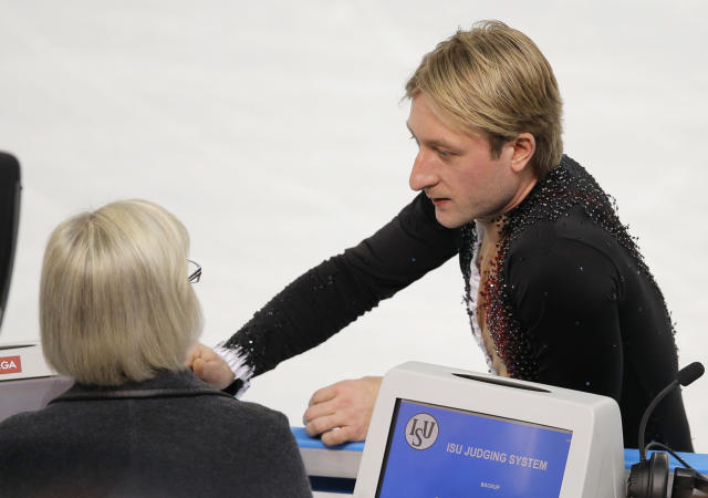 Evgeni Plushenko of Russia speaks with an official prior to pulling out of the men's short program figure skating competition due to illness at the Iceberg Skating Palace during the 2014 Winter Olympics, Thursday, Feb. 13, 2014, in Sochi, Russia. (AP Photo/Vadim Ghirda)