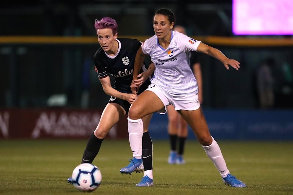 TACOMA, WASHINGTON - SEPTEMBER 21: Megan Rapinoe #15 of Seattle Reign FC and Carli Lloyd #10 of Sky Blue FC battle for the ball in the first half during their game at Cheney Stadium on September 21, 2019 in Tacoma, Washington. (Photo by Abbie Parr/Getty Images)