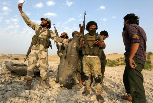 Rebel fighters pose for selfies with the remnants of the downed Syrian regime plane