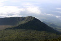 FILE - This Dec. 11, 2016 file photo shows the Virunga National Park, taken from the rim of the crater of the Nyiragongo volcano and looking over the crater of another, extinct volcano, taken in North Kivu Province, Democratic Republic of the Congo. Climate change is increasingly damaging the U.N.'s most cherished heritage sites, a leading conservation agency warned Wednesday Dec. 2, 2020, reporting that Australia's Great Barrier Reef and dozens of other natural wonders are facing severe threats. (Juergen Baetz/dpa via AP, File)