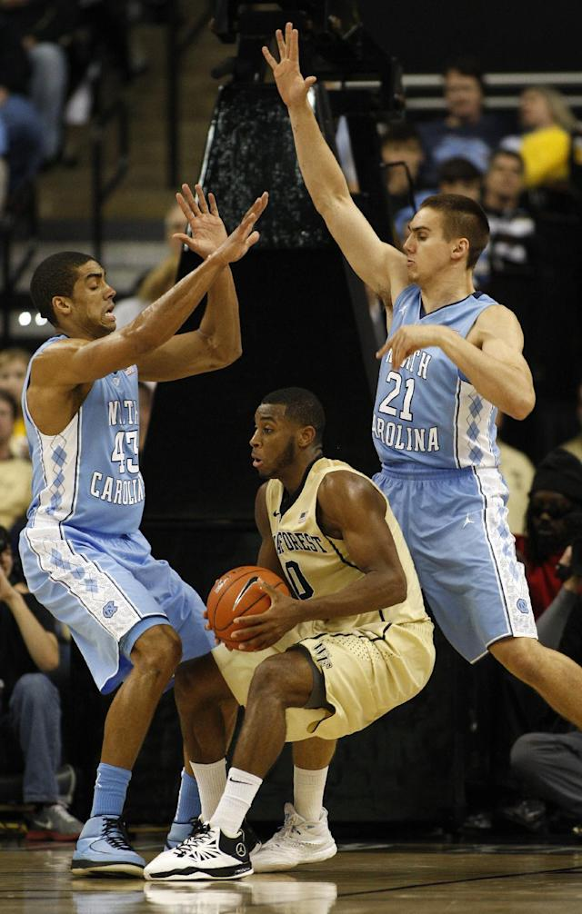 Wake Forest guard Codi Miller-McIntyre, center, is double-teamed by North Carolina forwards James Michael McAdoo, left, and Jackson Simmons in the second half of an NCAA college basketball game, Sunday, Jan. 5, 2014, in Winston-Salem, N.C. Wake Forest won 73-67. (AP Photo/Nell Redmond)