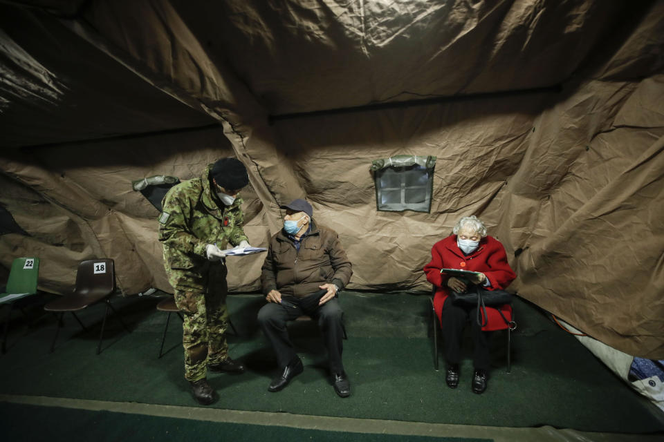 Over eighty-year-olds wait to be administered a dose of the Pfizer/BioNTech vaccine, in a tent set up at the Baggio military hospital in Milan, Italy, Thursday, Feb. 18, 2021. (AP Photo/Luca Bruno)