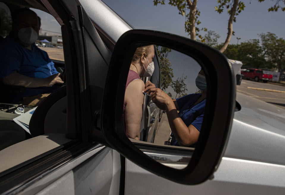 A woman is reflected in a side view car mirror as she is injected with her second dose of the Sinovac COVID-19 vaccine at a drive-thru vaccination site on the grounds of the National Stadium in Santiago, Chile, Wednesday, March 10, 2021. (AP Photo/Esteban Felix)