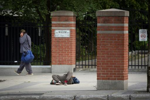 A pedestrian walks past a passed-out drug user on June 25, 2020 in Ottawa, Canada; an emergency government pandemic payment has been used by some addicts to buy drugs, and overdoses have surged