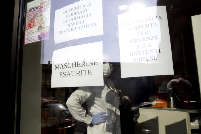 "A note reading in Italian "" Masks sold out "" and ""pharmacy is open for urgencies but shutters are closed"", right, hang on the window of a pharmacy in Codogno, near Lodi, Northern Italy, Saturday, Feb. 22, 2020. A dozen northern Italian towns were on effective lockdown Saturday after the new virus linked to China claimed two fatalities in Italy and sickened an increasing number of people who had no direct links to the origin of the virus. The secondary contagions prompted local authorities in towns in Lombardy and Veneto to order schools, businesses and restaurants closed, and to cancel sporting events and Masses. (AP Photo/Luca Bruno)"