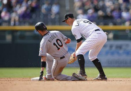 Jun 24, 2018; Denver, CO, USA; Miami Marlins infielder JT Riddle (10) slides into second base ahead of the tag by Colorado Rockies infielder DJ LeMahieu (9) for an RBI double in the fourth inning at Coors Field. Mandatory Credit: Russell Lansford-USA TODAY Sports