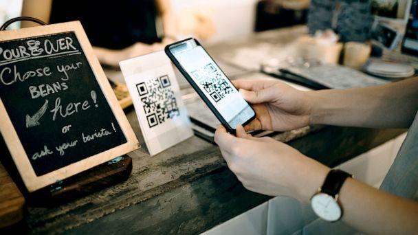 PHOTO: A customer scans a QR code to make a contactless payment with her smartphone in a cafe in an undated stock image. (STOCK IMAGE/Asiavision via Getty Images)