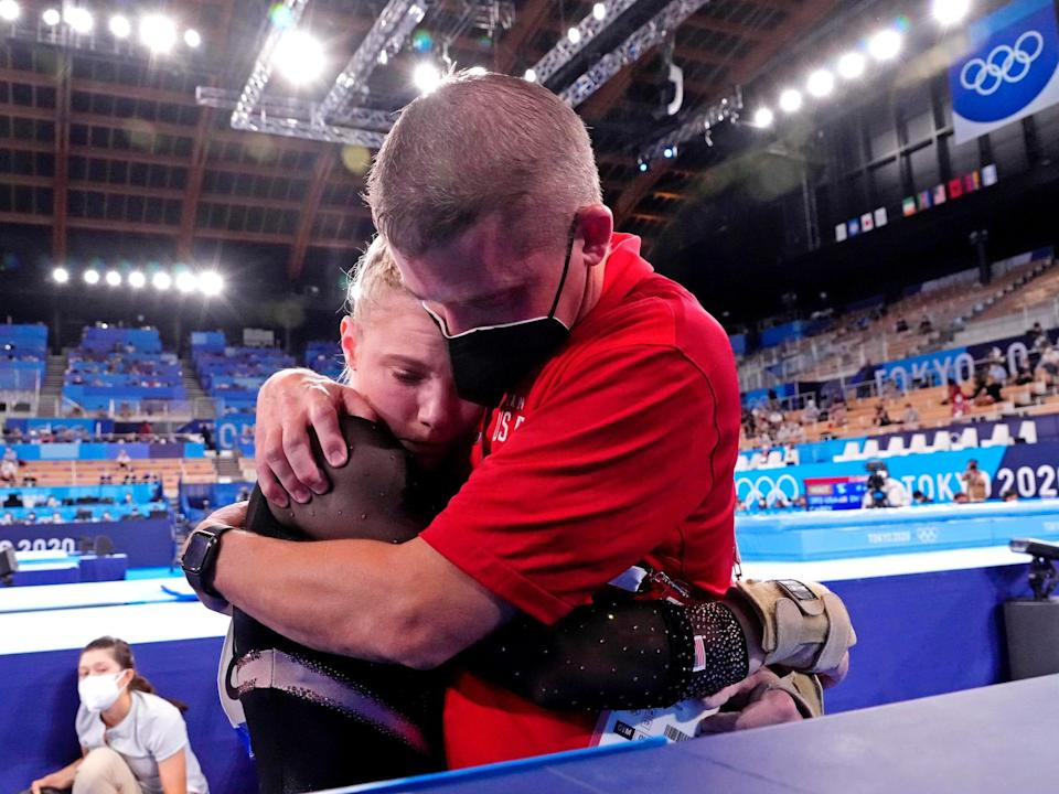 Brian Carey (right) - Jade Carey's father and coach - comforts his daughter after her vault mishap.