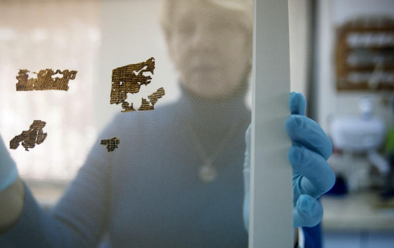 A worker of the Dead Sea Scrolls conservation laboratory at the IAA, Israel Antiquities Authority, holds a frame with small fragments of the Dead Sea Scrolls in a laboratory in Jerusalem, Tuesday, Dec. 18, 2012. Israeli authorities say they have put 5,000 fragments of the ancient Dead Sea scrolls online in a partnership with Google.(AP Photo/Dan Balilty)