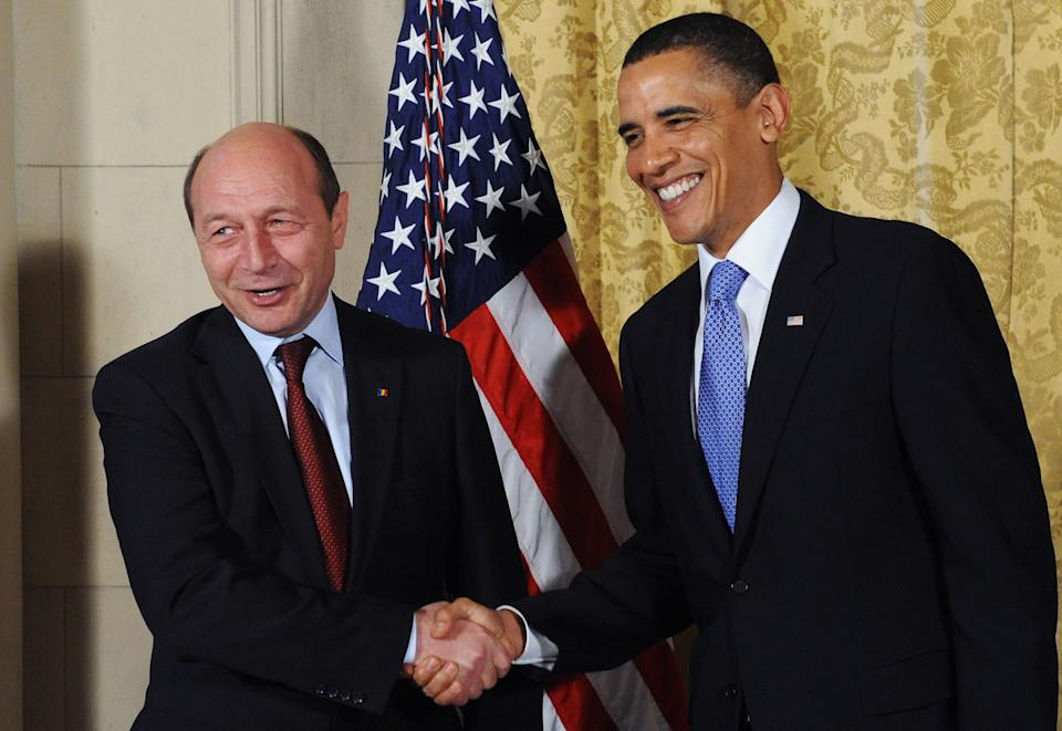 U.S. President Barack Obama (R) greets Romania's President Traian Basescu before a dinner at the U.S. Ambassador's residence in Prague on April 8, 2010.
