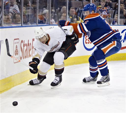 Anaheim Ducks' Andrew Cogliano (7) chases the puck as he is checked by Edmonton Oilers' Ladislav Smid during the first period of their NHL hockey game in Edmonton, Alberta, Sunday, April 21, 2013. (AP Photo/The Canadian Press, Jason Franson)