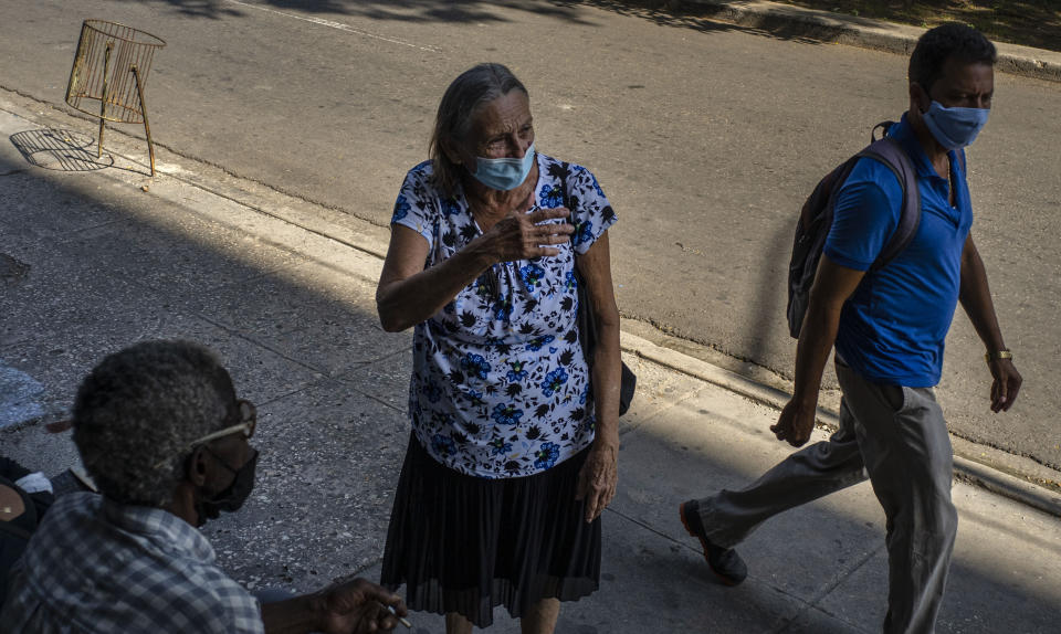 People wearing masks as a precaution amid the new coronavirus pandemic speak on the street as they wait to enter a COVID-19 vaccination center set up inside a cultural center in Havana, Cuba, Monday, Aug. 2, 2021. (AP Photo/Ramon Espinosa)
