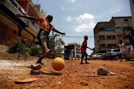 Remi Bamba scores a goal during a football match in a street of a neighborhood in Abidjan, Ivory Coast May 21, 2018. REUTERS/Luc Gnago
