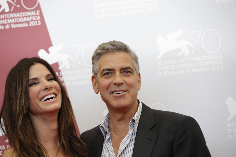 Actors Sandra Bullock and George Clooney poses for photographers at the photo call for the film Gravity during the 70th edition of the Venice Film Festival held from Aug. 28 through Sept. 7, in Venice, Italy, Wednesday, Aug. 28, 2013. (AP Photo/Andrew Medichini)